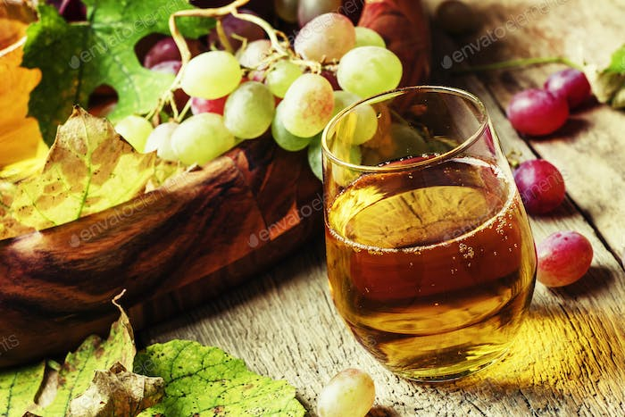 Grape juice in glass and berries with leaves