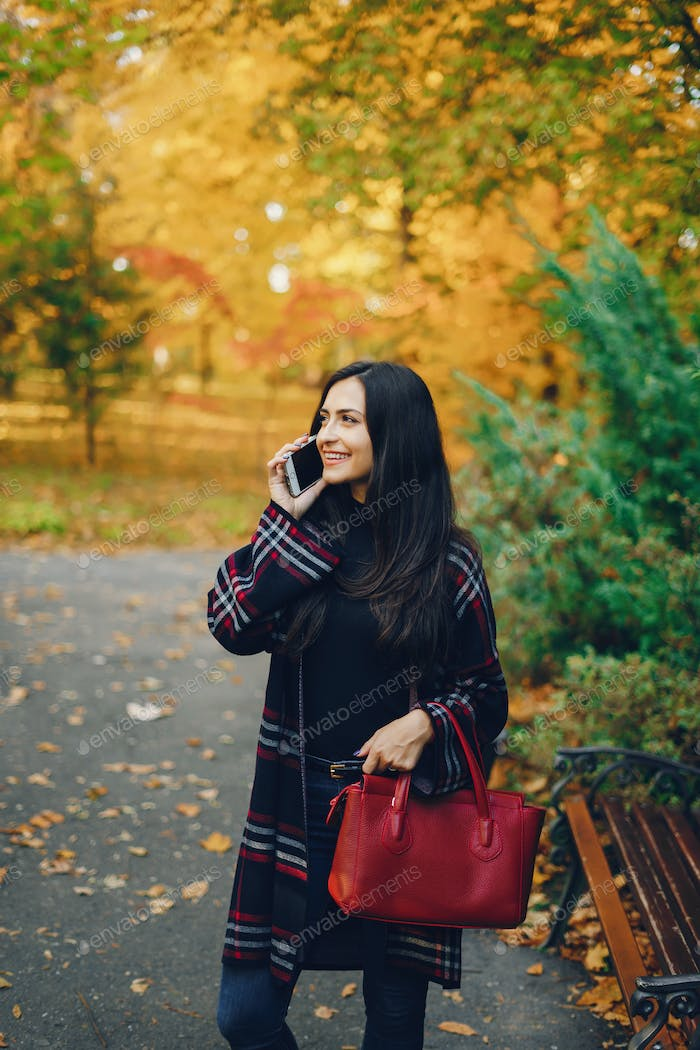 girl using her cell phone while walking through the park