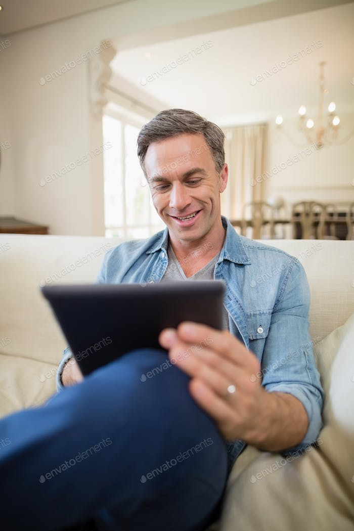 Man sitting on sofa and using digital tablet in living room