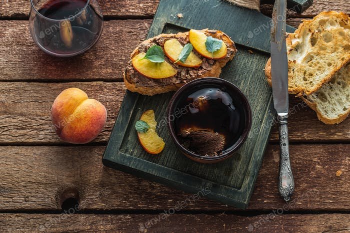 Chicken liver pate with griiled bread and peach, rustic style