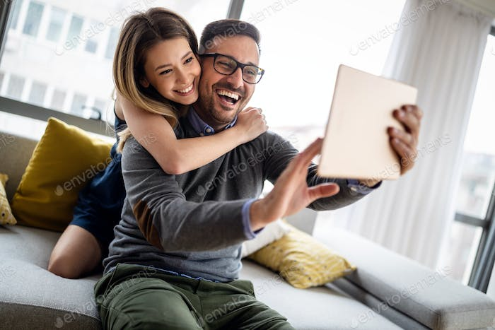 Young couple watching media content online in a tablet at home