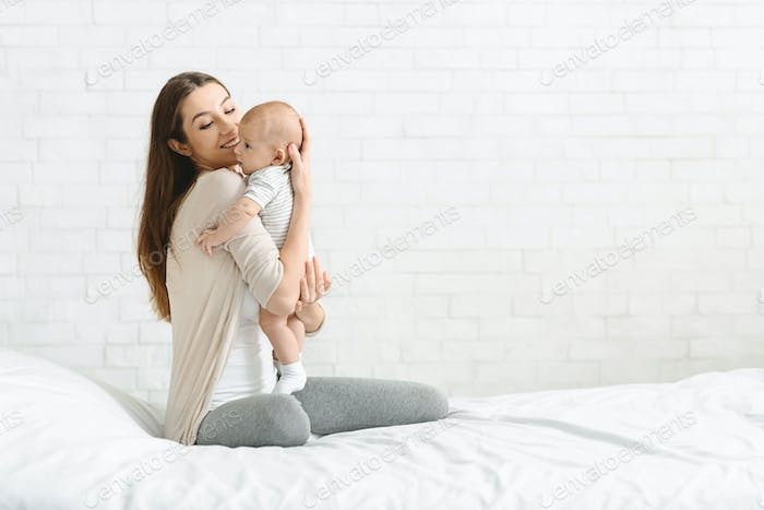Young woman embracing adorable baby sitting on bed at home