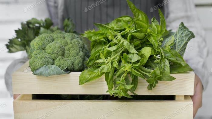 Woman holding broccoli and greens in organic wooden box