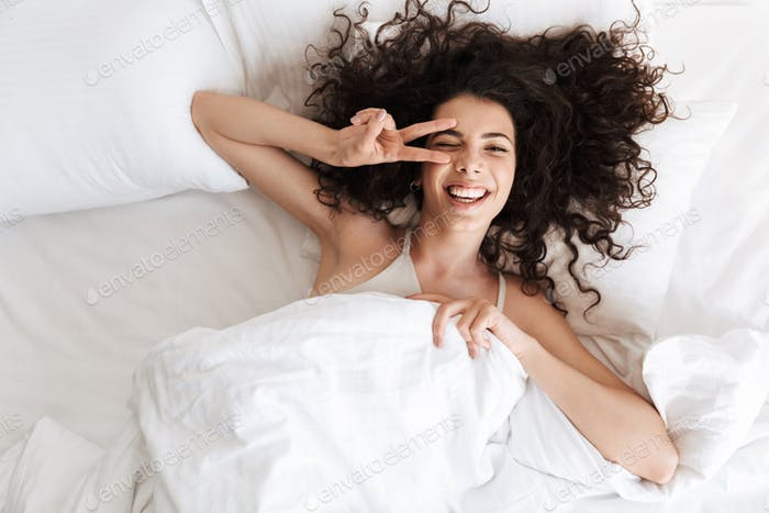 Image from top of happy woman 20s with dark curly hair lying in