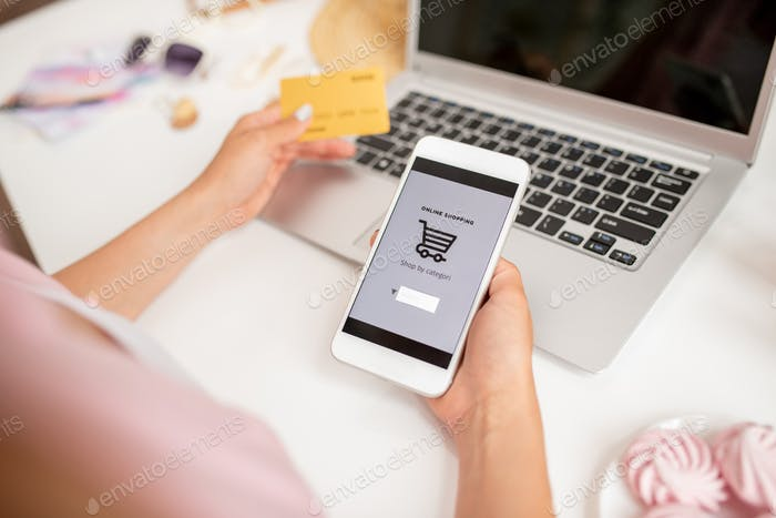 Smartphone held by young contemporary mobile shopper searching for goods