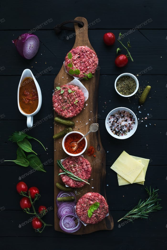 Ingredients for cooking burgers. Raw ground beef meat cutlets