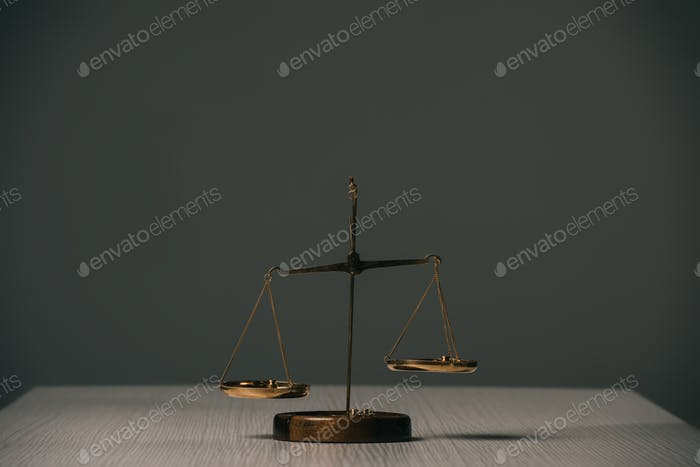 empty scales of justice on wooden table on grey