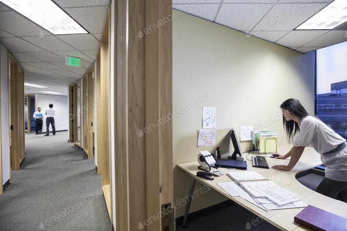 An asian businesswoman working alone in her office next to a long hallway.