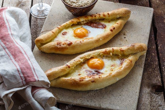 Two ajarian khachapuri, georgian bread with cheese and yolk
