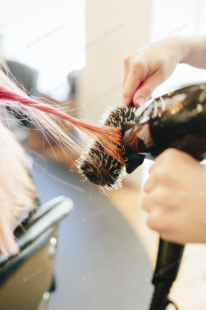 A hair stylist blowdrying a client's long straight pink hair using a round bristle brush.