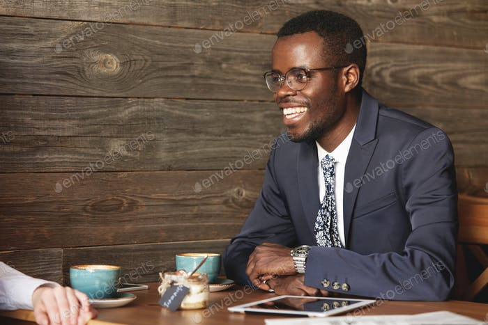 African businessman in formal suit smiling to his job partner discussing collaboration and profit op