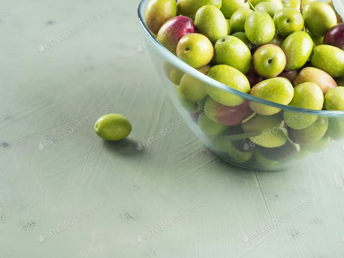 Freshly picked raw green olives in glass bowl