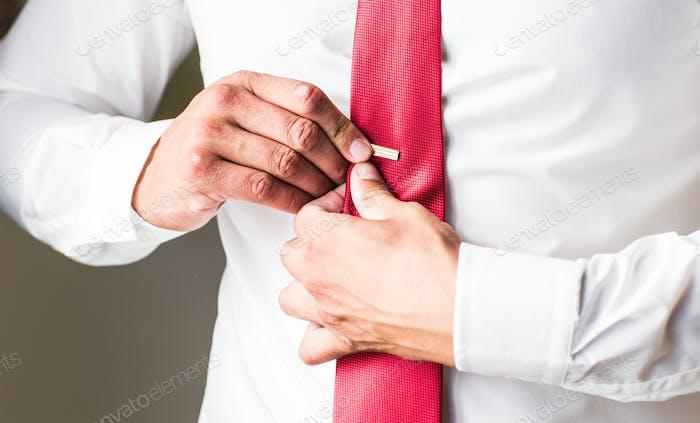 Man putting on tie clip, closeup