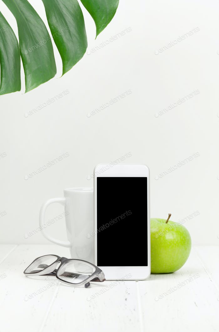 Workplace with smartphone, apple and coffee cup
