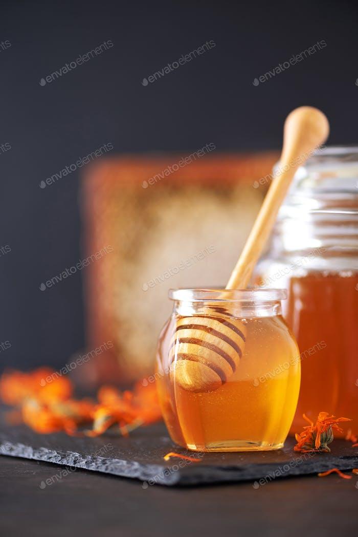 Herbal honey in jar with dipper, honeycomb, bee pollen granules, calendula flowers on black