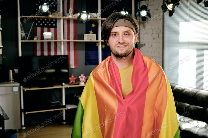 Happy young man wrapped into pride flag