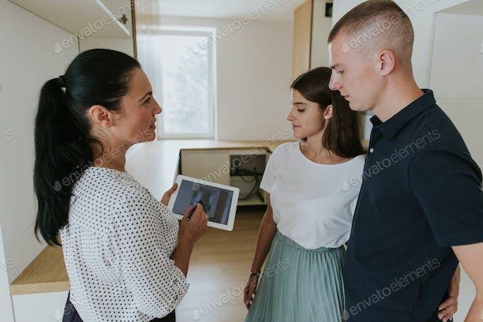 Agente inmobiliario usando tableta digital mostrando joven pareja nueva casa.