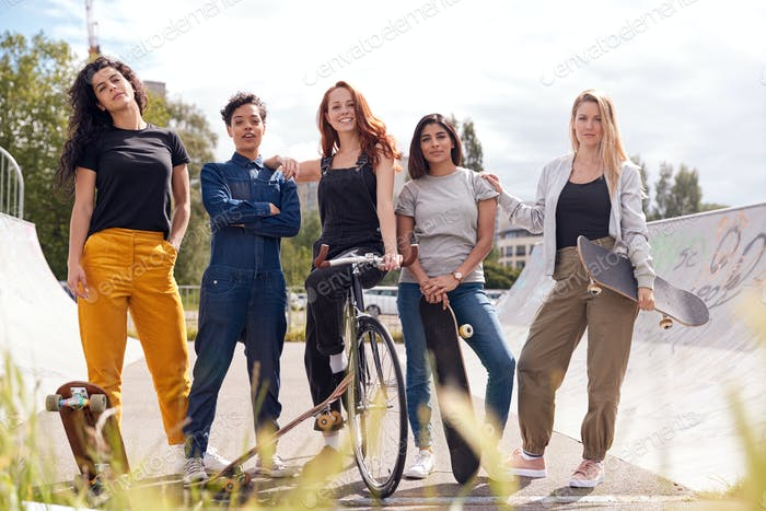 Portrait Of Female Friends With Skateboards And Bike In Urban Skate Park