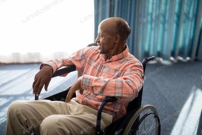 Smiling disabled senior man sitting on wheelchair against window