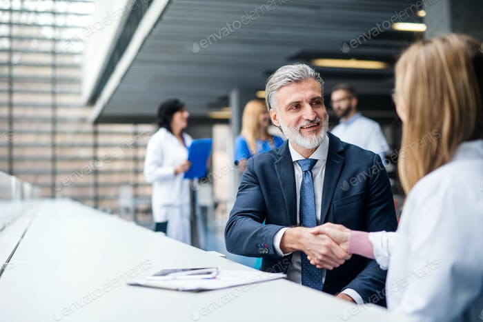 Doctors talking to pharmaceutical sales representative, shaking hands