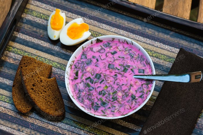 Cold beetroot soup with eggs and bread on a decorative tray.Soup kholodnik red on an unusual tray