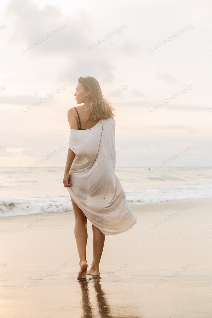 Young beautiful girl at the seaside waves.