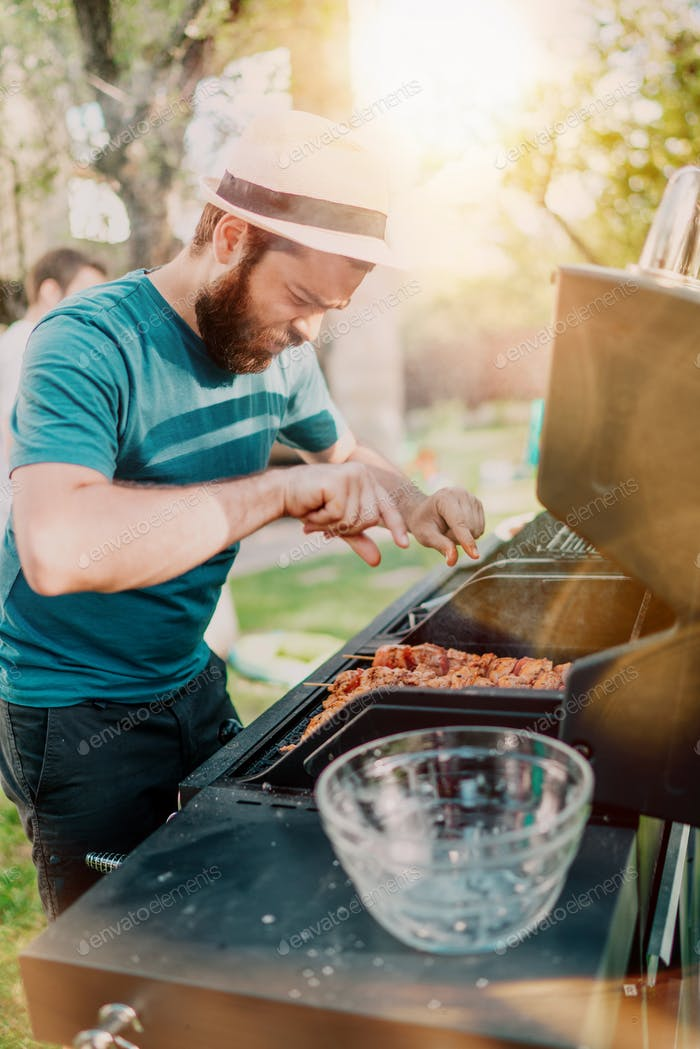 Man smiling and cooking at barbecue grill party. Friends, people lifestyle concept