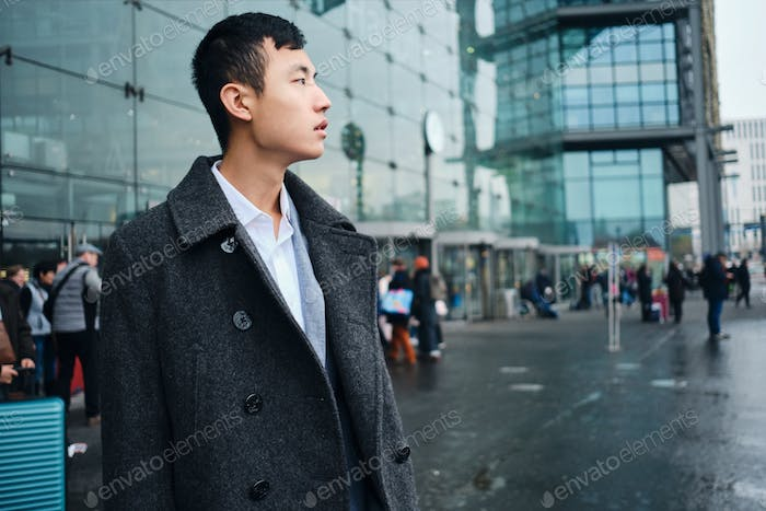 Side view of young Asian businessman confidently looking away waiting taxi near airport