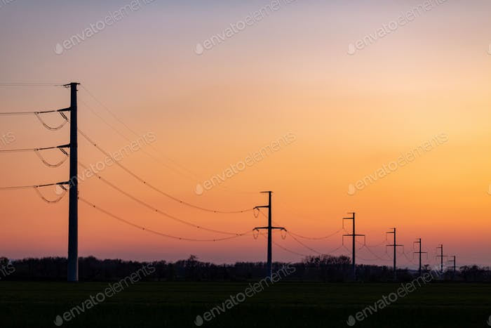 High voltage power tower over sunset clear sky, blackout concept