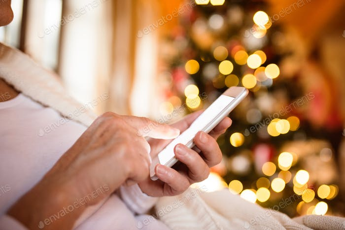 Unrecognizable woman with smartphone in front of Christmas tree.
