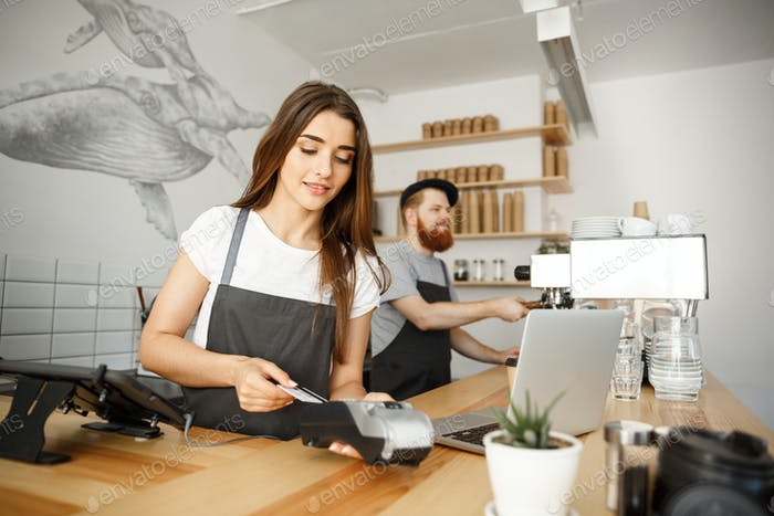 Coffee Business Concept - Beautiful female barista giving payment service for customer with credit