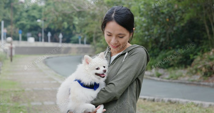 Woman go out with Pomeranian dog