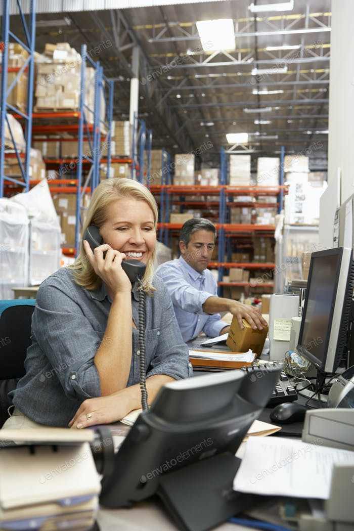 Деловая женщина, работающая на столе в склад