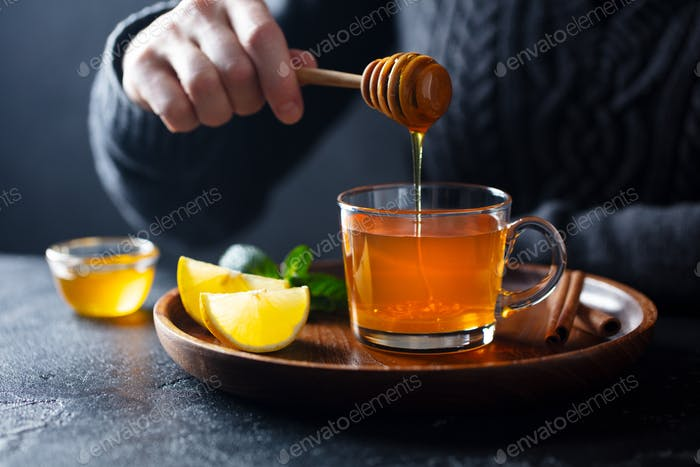 Cup of Tea with Pouring Honey and Lemon. Grey Background.