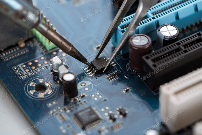 Soldering typical desktop computer baseboard close-up view
