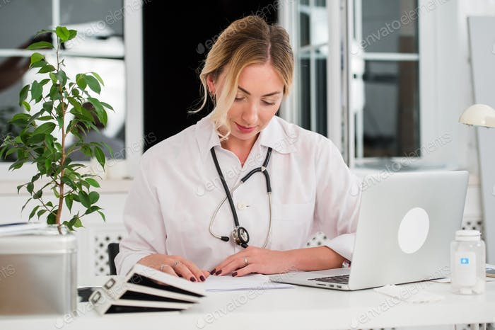 Mid adult female doctor reading documents at office desk