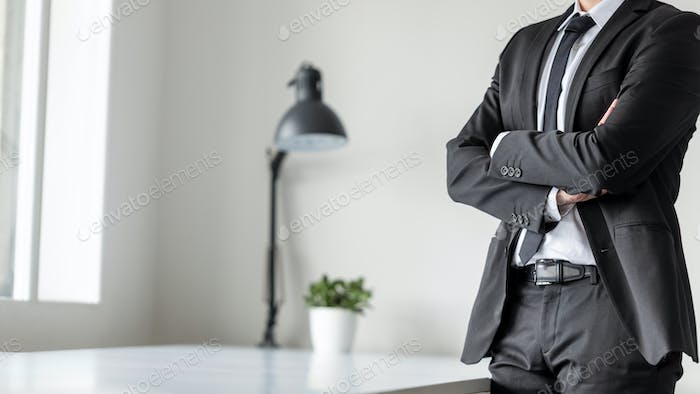 Businessman standing in office with crossed arms