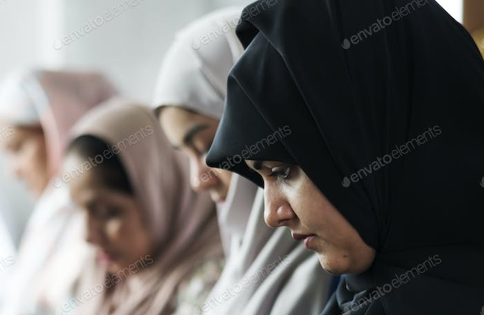 Muslim women praying in Tashahhud posture