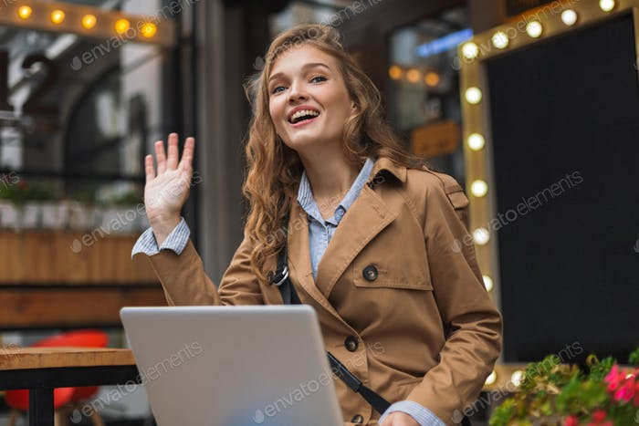 Young attractive woman in trench coat happily waving hand sittin