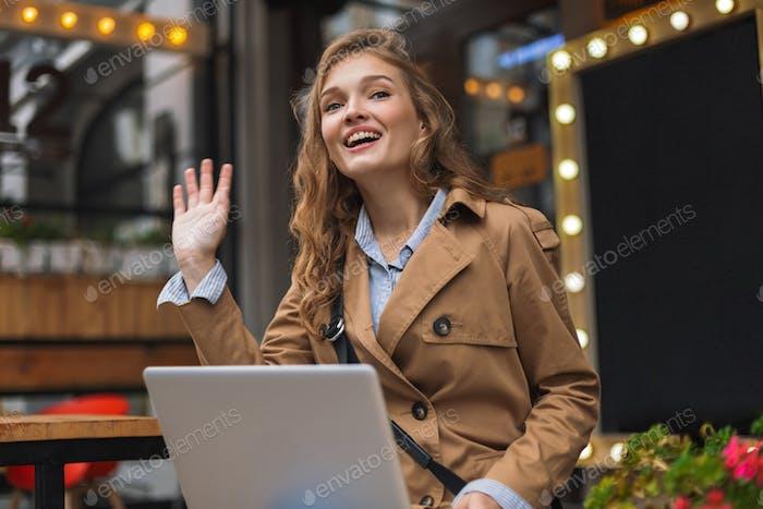 Mujer atractiva joven en gabardina felizmente agitando la Mano sittin
