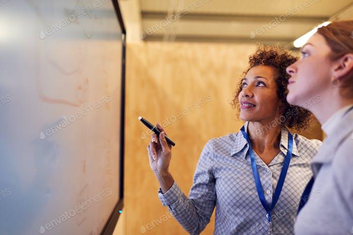 Tutor mit weiblichen Trainee Elektriker Blick auf Schaltplan auf Bildschirm
