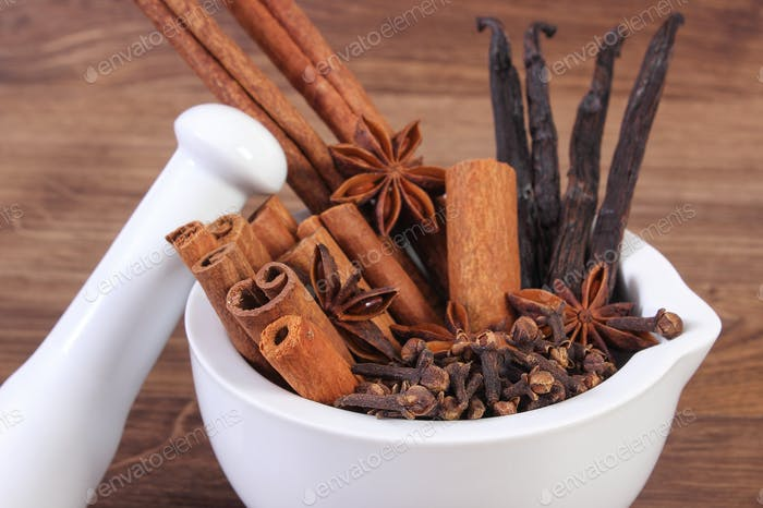 Fragrant anise, cloves, cinnamon and vanilla sticks in mortar on rustic board