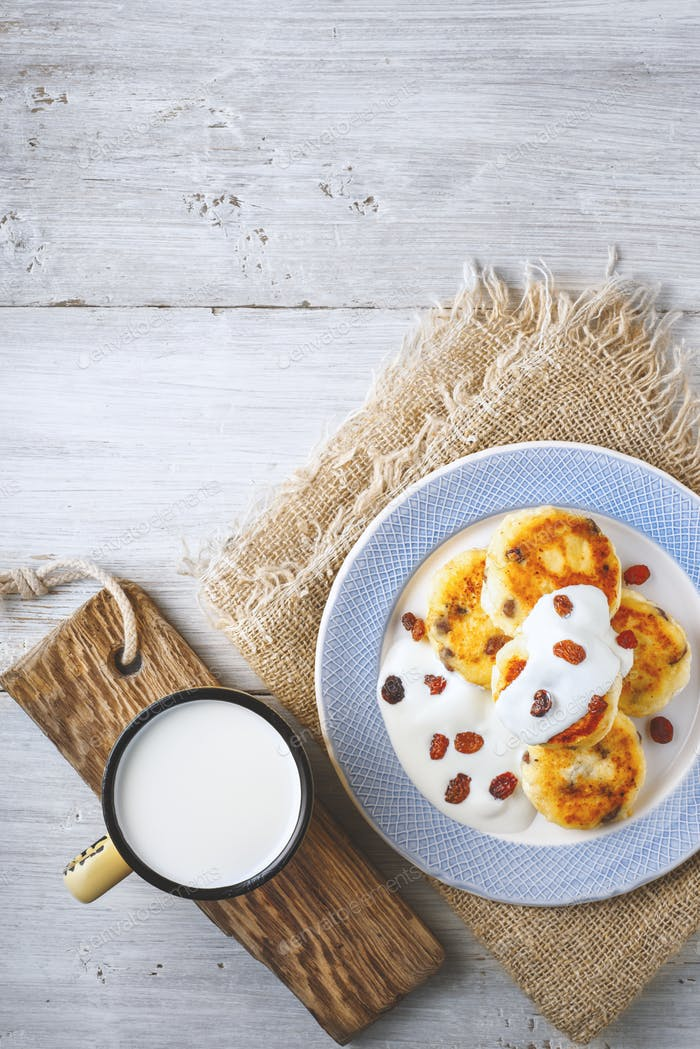 Cheese pancakes with raisins and yogurt on a ceramic plate