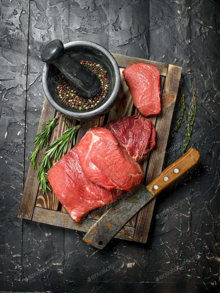 Raw meat. Fresh beef on a wooden tray with fragrant peppercorn and rosemary branches.