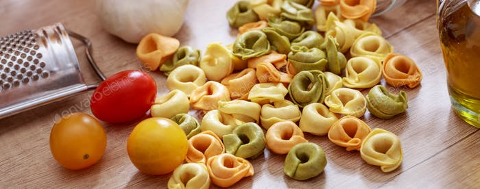 Colorful tortellini pasta, tomatoes and olive oil on the table, banner
