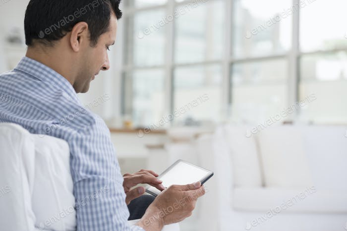 Professionals in the office. A light and airy place of work. A man seated using a digital tablet.