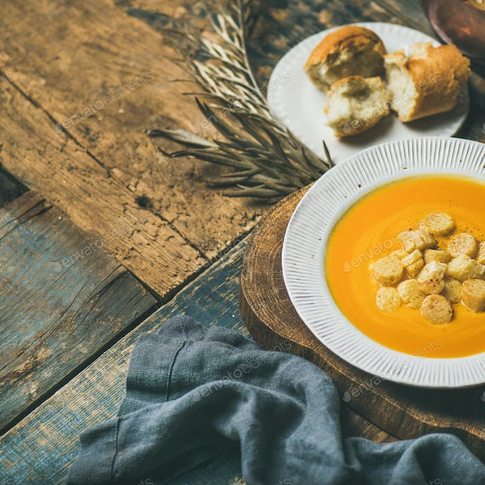 Fall pumpkin cream soup with croutons and seeds, square crop