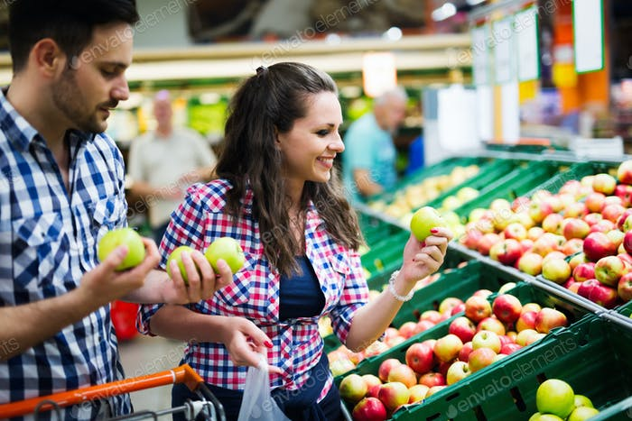 Couple shopping for veggies and fruit in supermarket