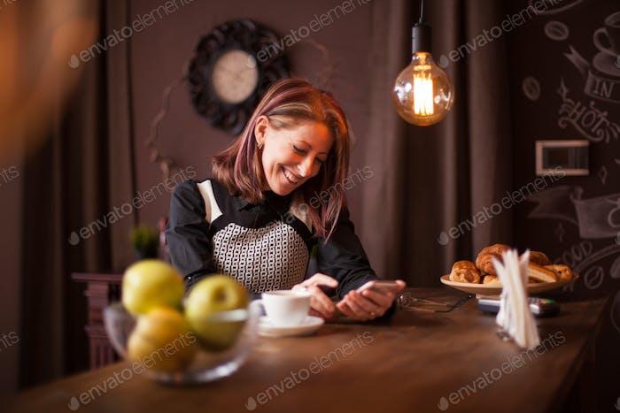 Erwachsene Geschäftsfrau lacht beim Blick auf ihr Handy