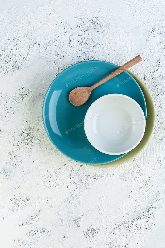 Two plates, a bowl and a wooden spoon on a light gray textural b